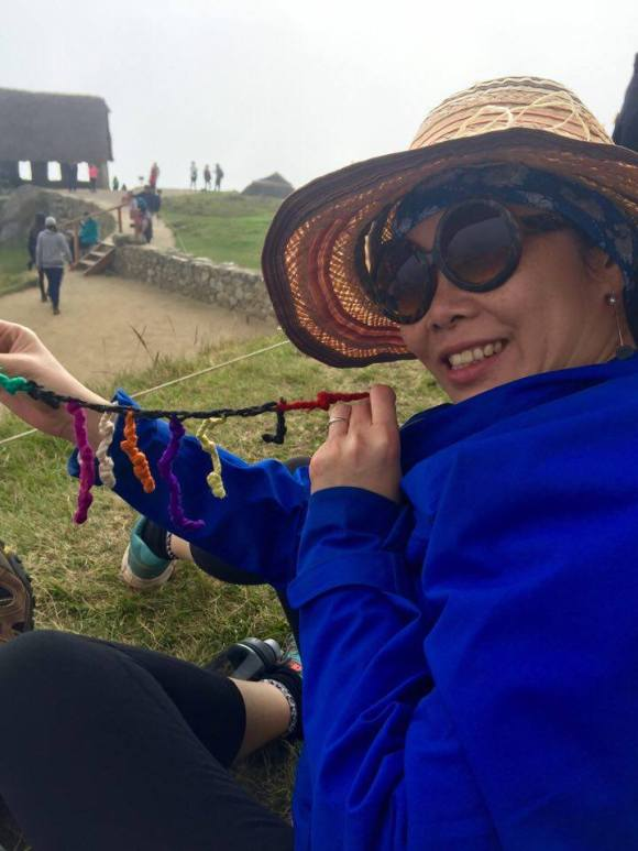 Anna with a replica of a system of coloured strings that the Incas used for communication