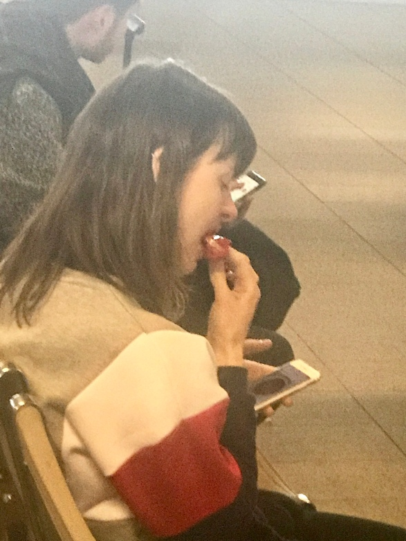 A woman munching down on a chili in Amsterdam Airport Schiphol